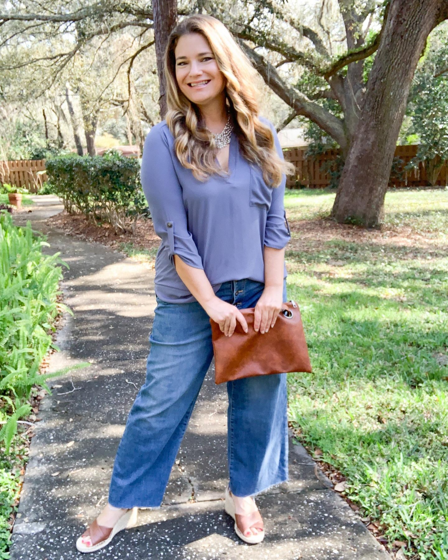 Four chic and effortless ways to wear wide leg jeans. See how to style wide leg jeans into outfits that are on trend and make an impact. Tunic, espadrilles, clutch spring outfit.