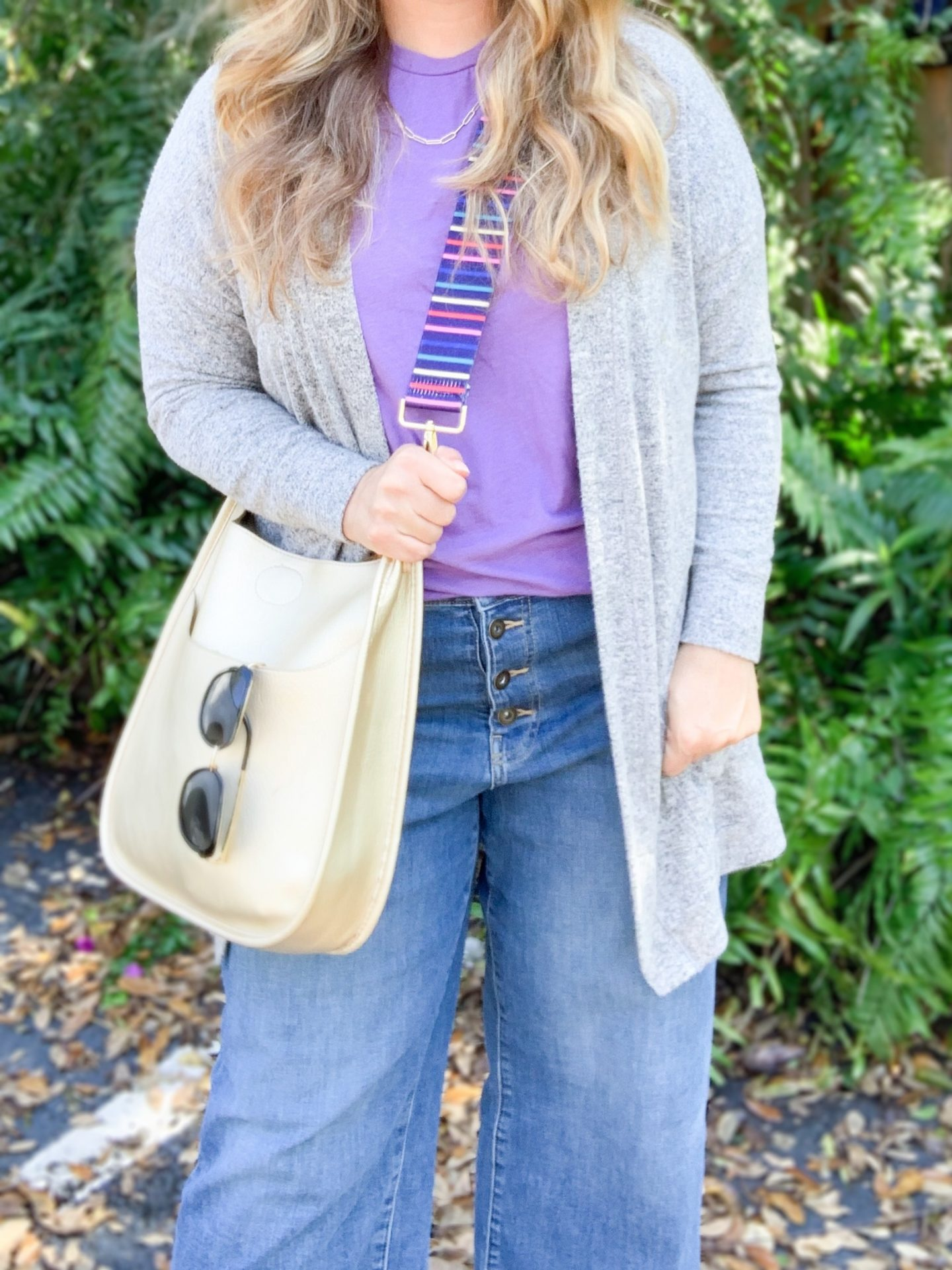 Four chic and effortless ways to wear wide leg jeans. See how to style wide leg jeans into outfits that are on trend and make an impact. Long cardigan, t-shirt, and crossbody social threads vegan messenger bag spring outfit.