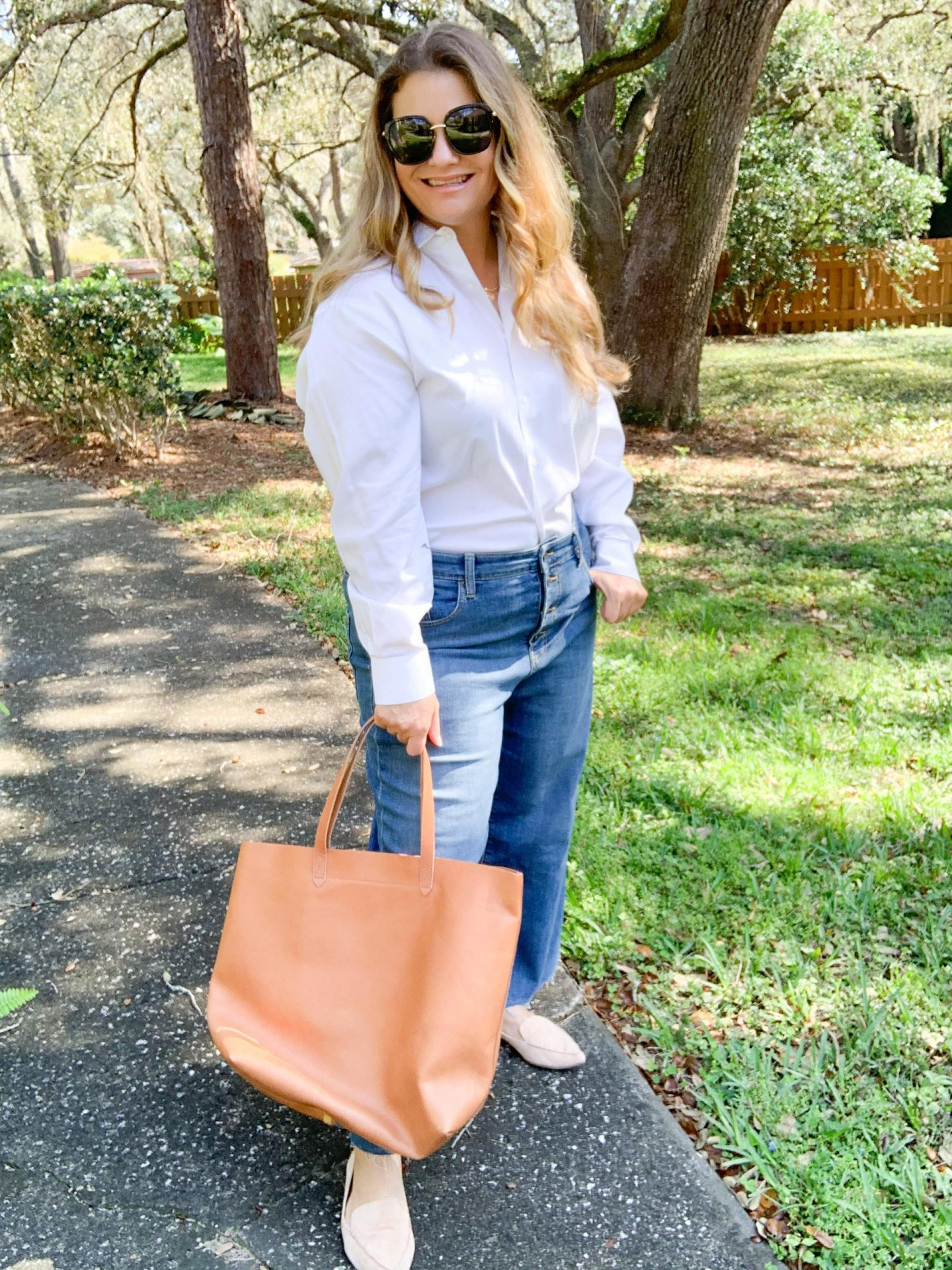 Four chic and effortless ways to wear wide leg jeans. See how to style wide leg jeans into outfits that are on trend and make an impact. Men's white button down Oxford shirt, loafers, Madewell tote spring outfit.